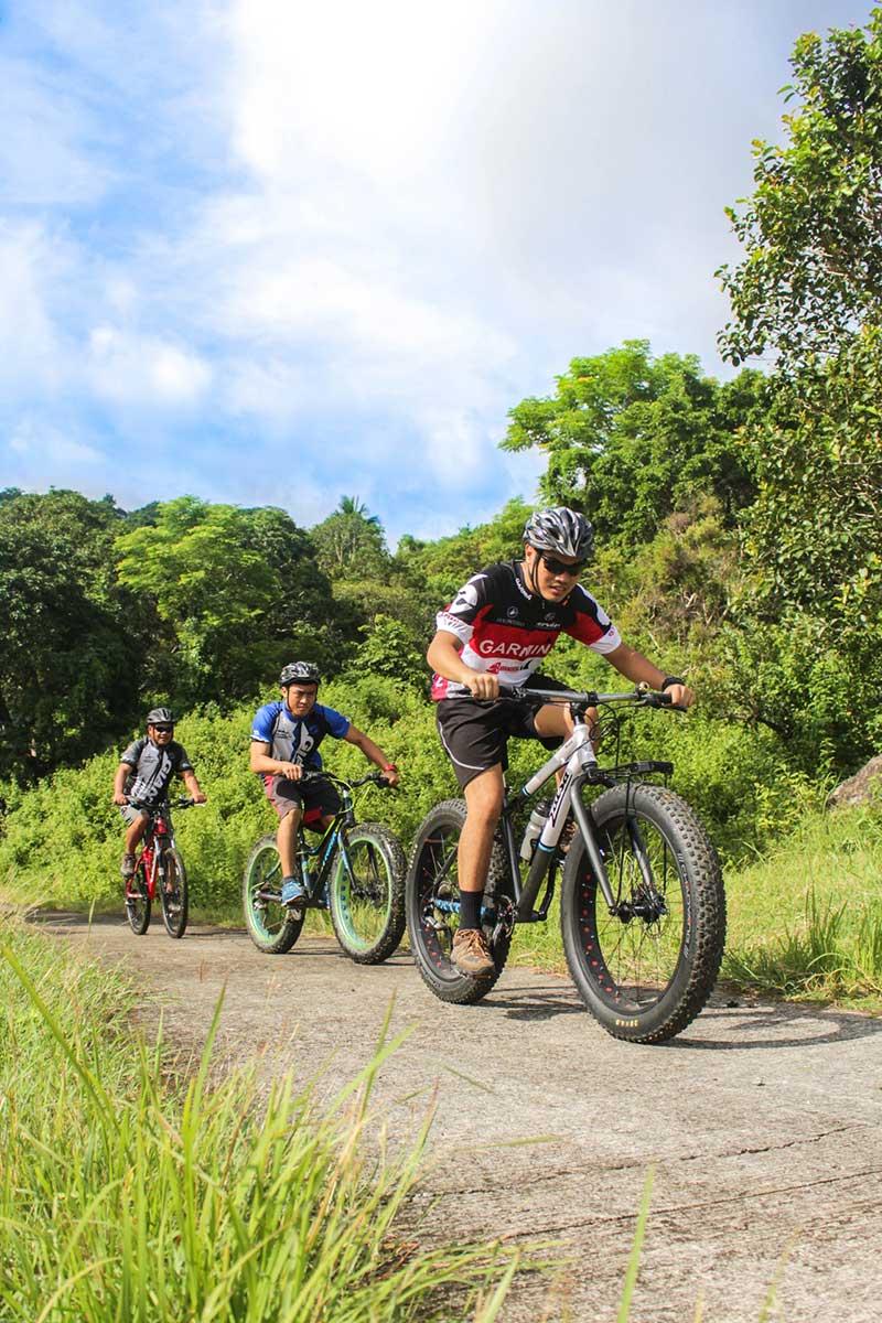 three men riding their bikes on the road