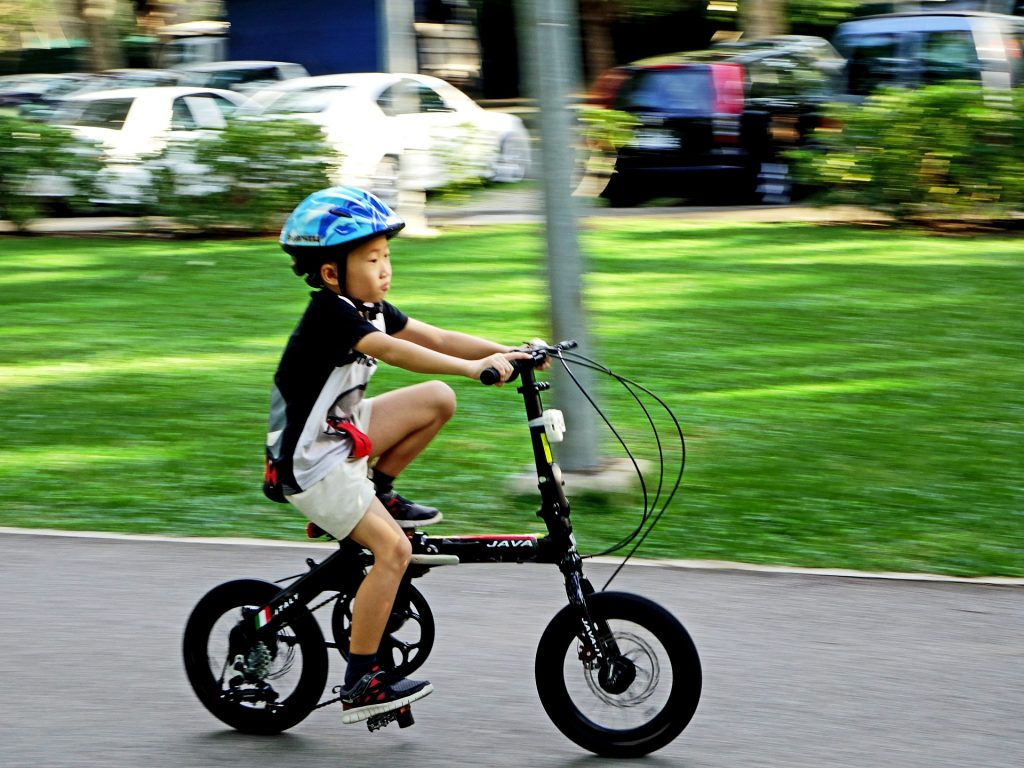 A boy riding a bike while wearing one of the best kids' bike helmets in blue