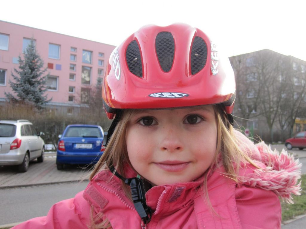 A little girl in a pink bike helmet