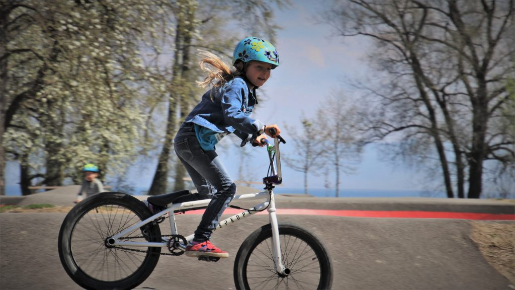 A girl riding a bike in one of the best kids' bike helmets